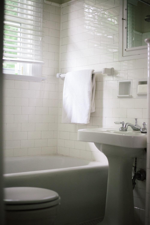 white towel on white ceramic bathtub