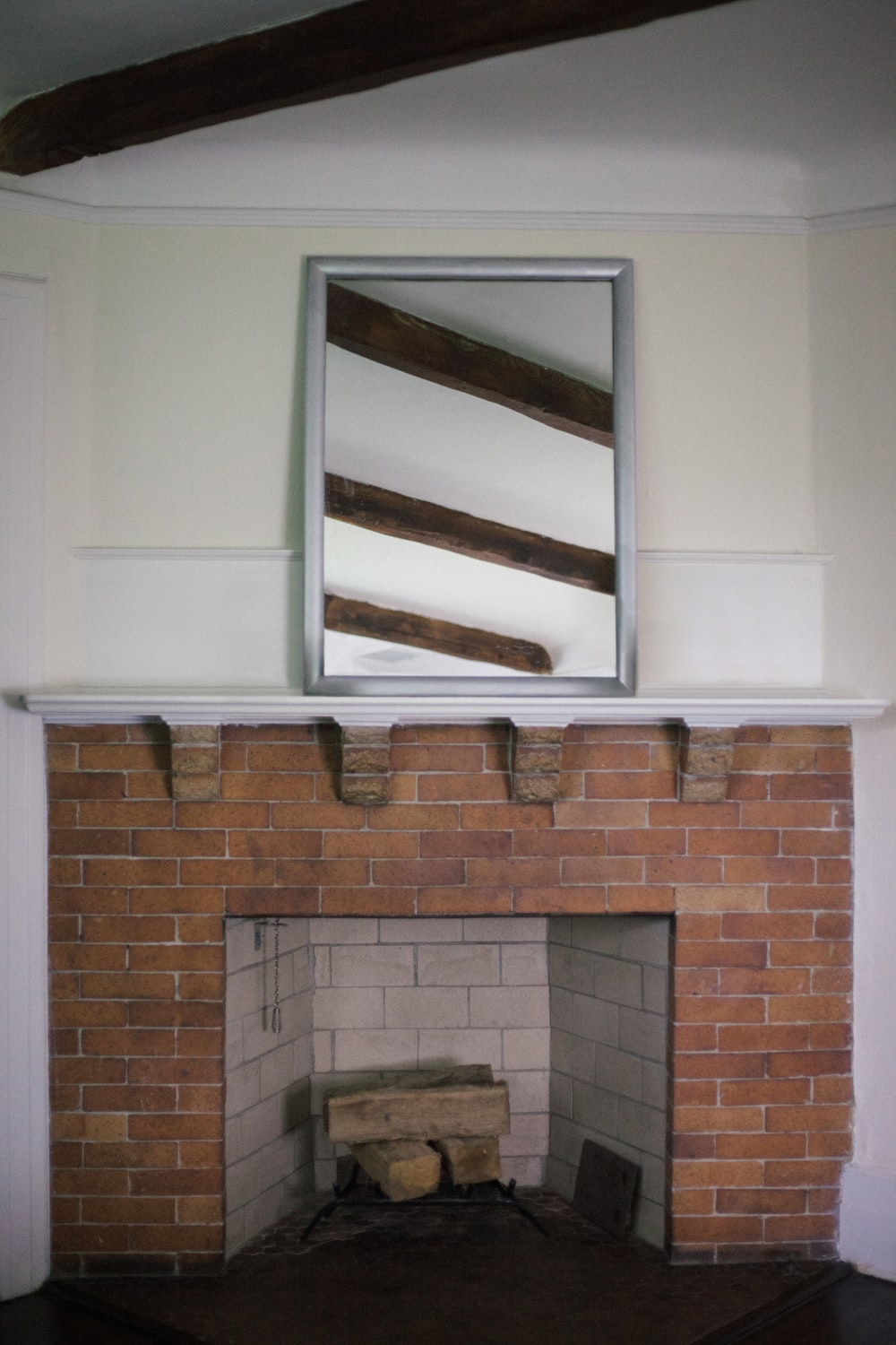 brown brick fireplace with white wooden frame