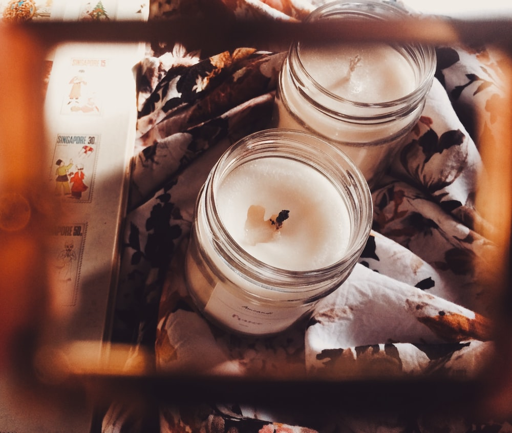 white candle in clear glass jar