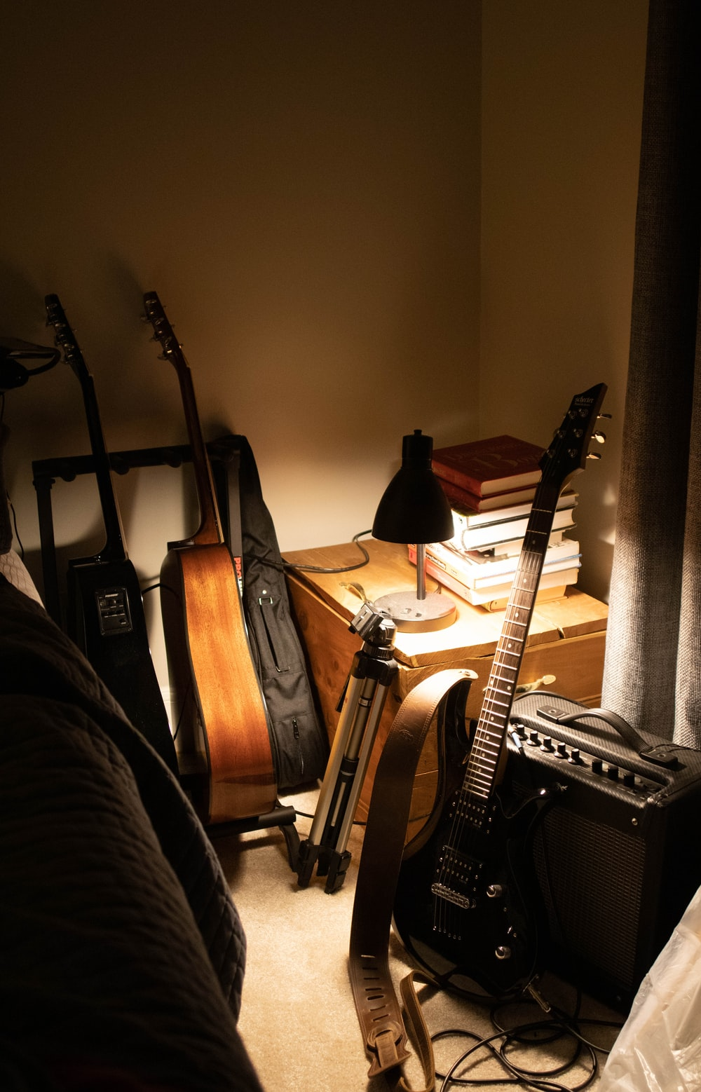 brown acoustic guitar beside black electric guitar