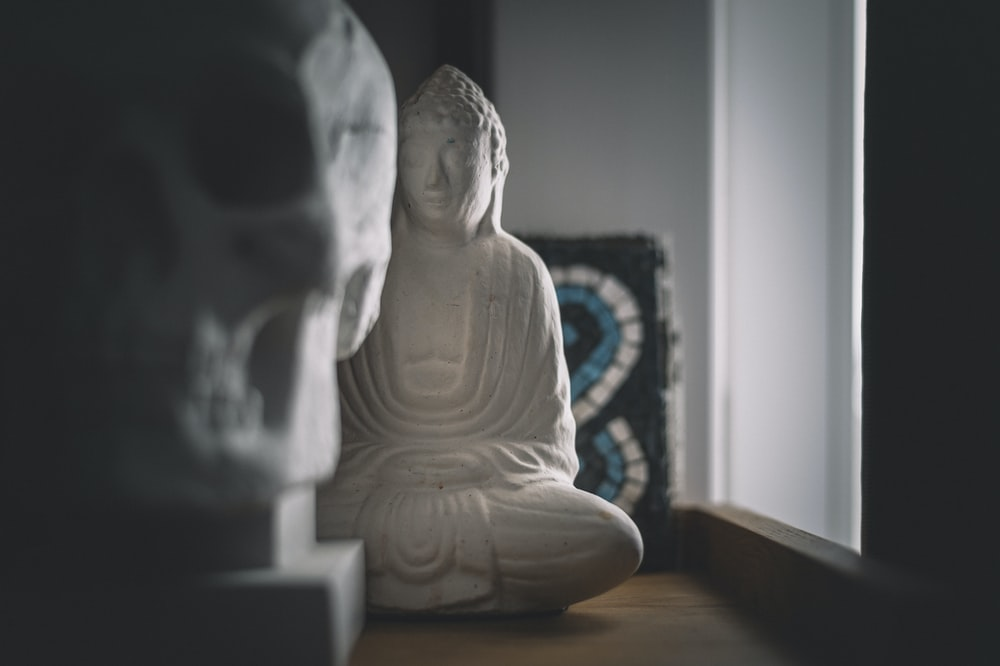 white ceramic buddha figurine on brown wooden table