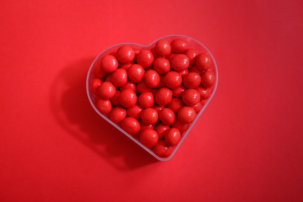 red round fruits on red plastic container