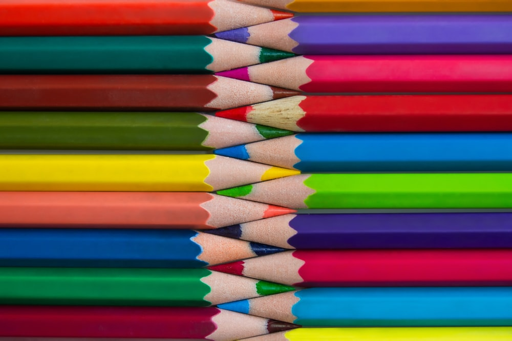 multi colored coloring pencils on brown wooden table