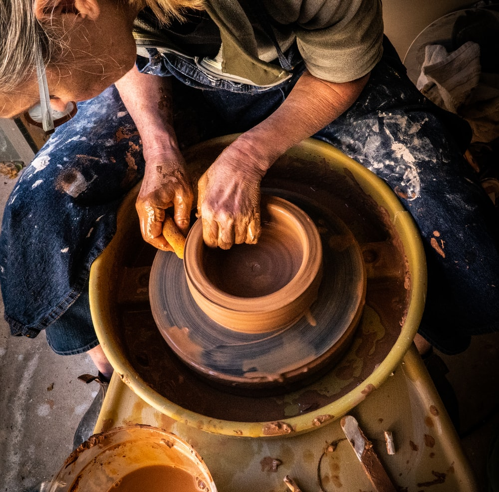 person in blue denim jeans making clay pot