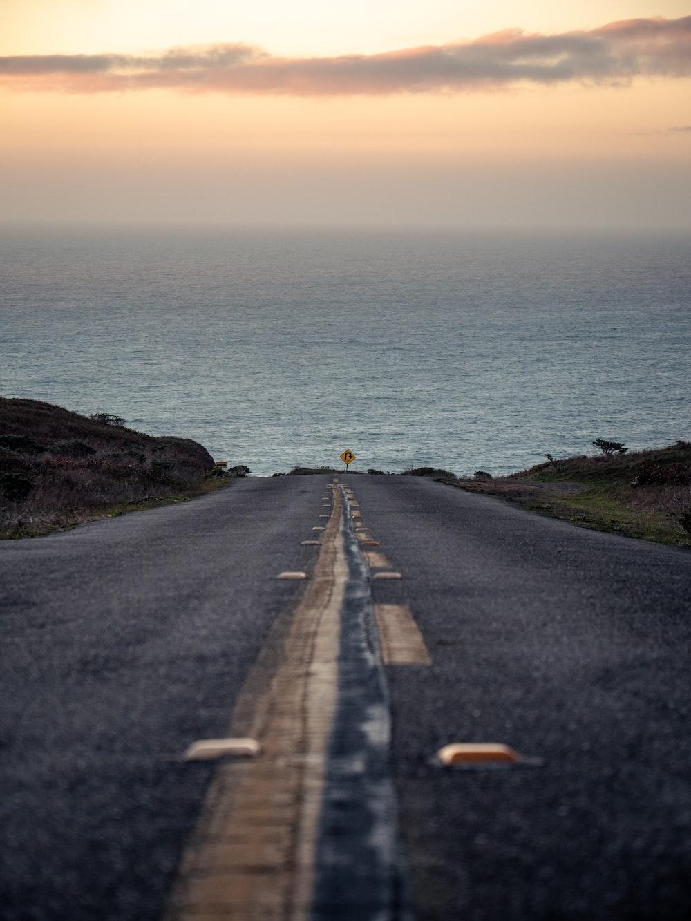 black asphalt road beside body of water during daytime