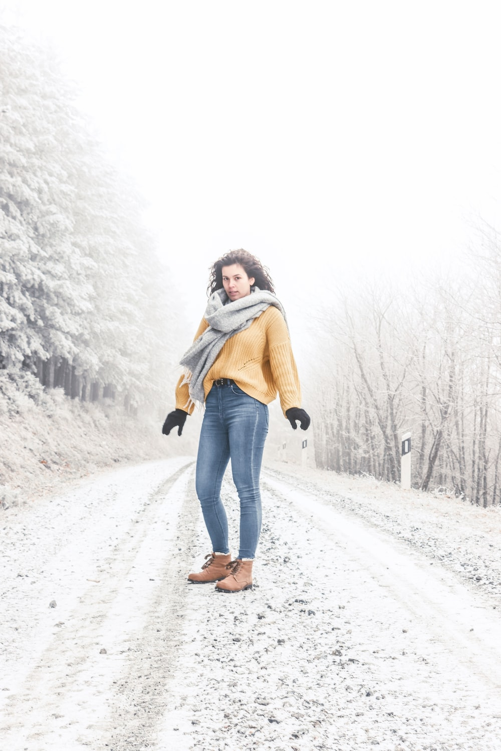 woman in brown scarf and black pants standing on snow covered ground during daytime