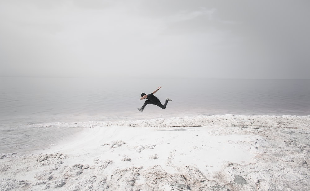 man in black shirt and black pants jumping on white sand beach during daytime