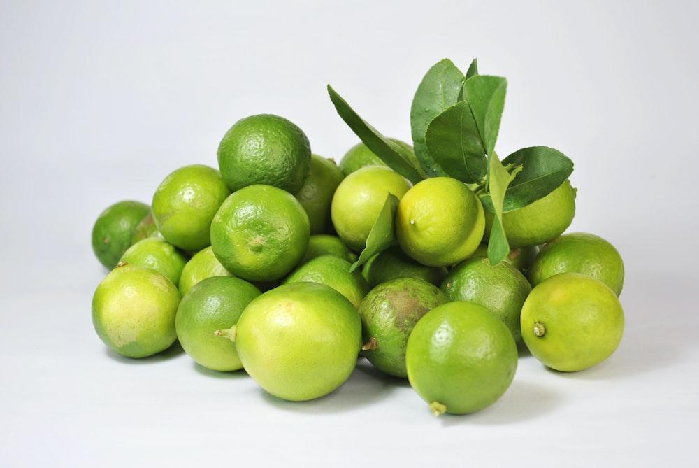green lemon fruit on white surface
