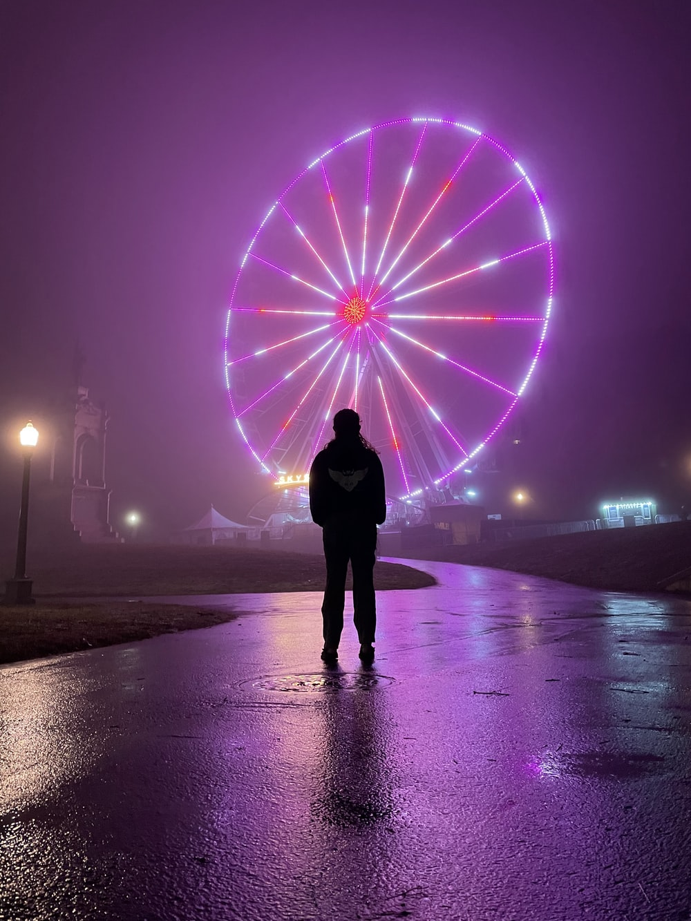person standing on beach with purple lights