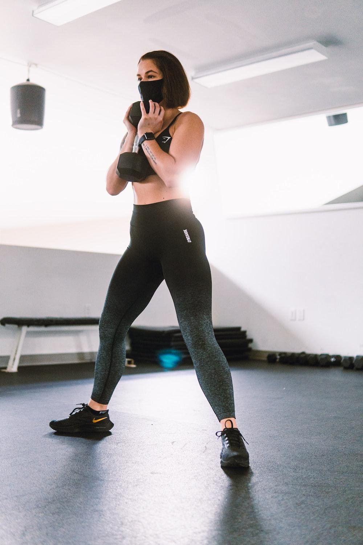 woman in black tank top and blue leggings doing yoga