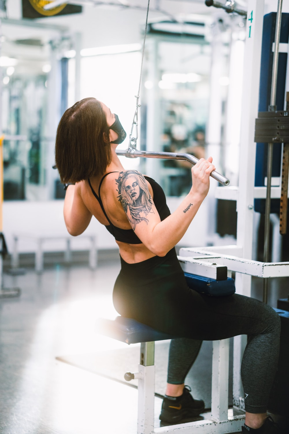 woman in black tank top and black leggings sitting on exercise equipment