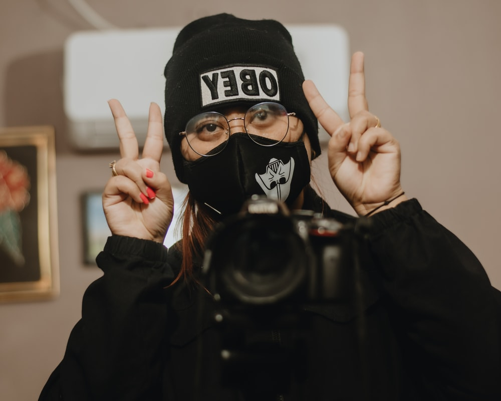 person in black and white hoodie wearing black and white skull mask