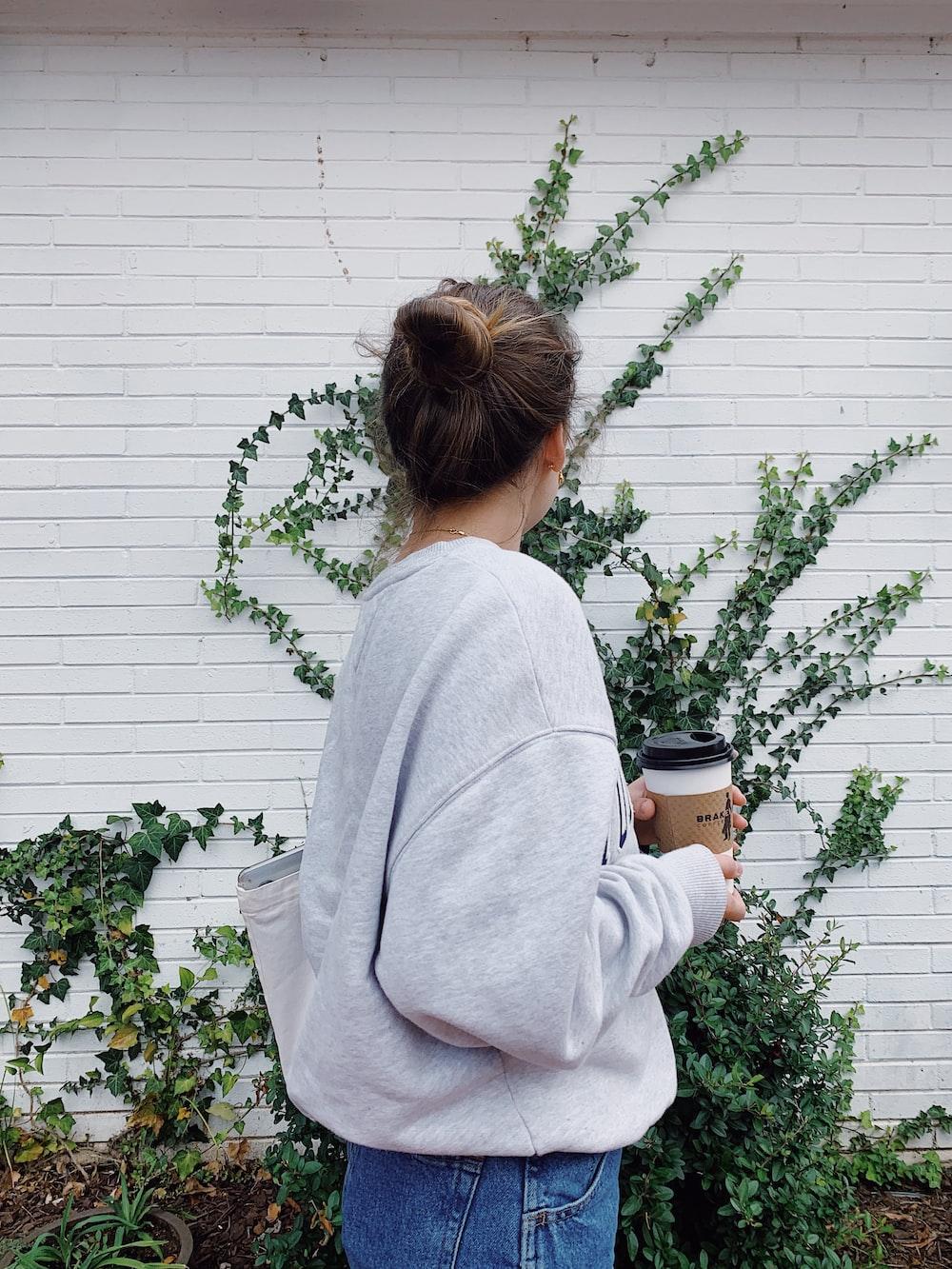 woman in gray sweater holding mug