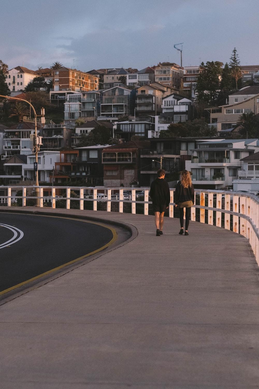 man in black jacket and black pants walking on gray asphalt road during daytime