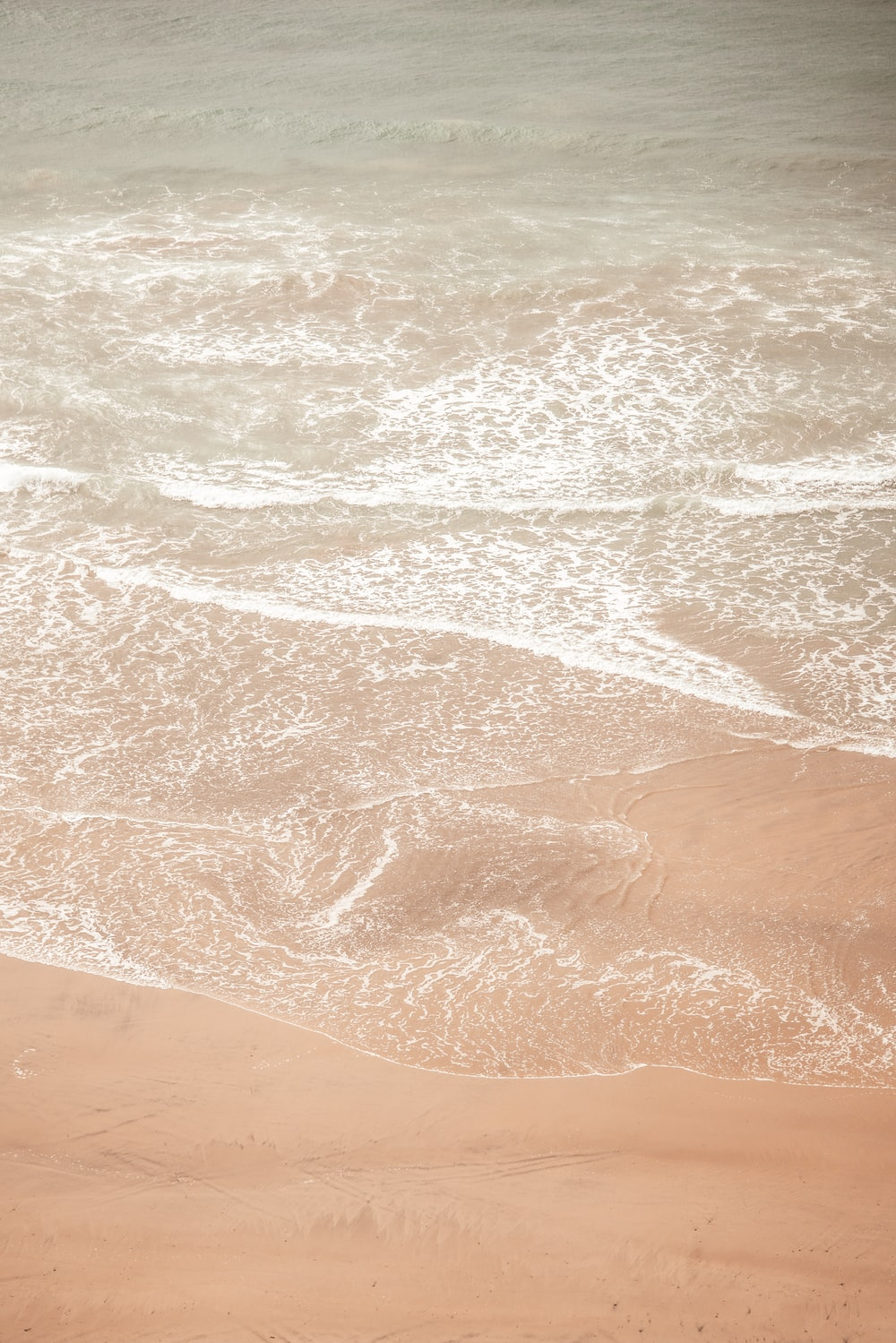 brown sand near body of water during daytime