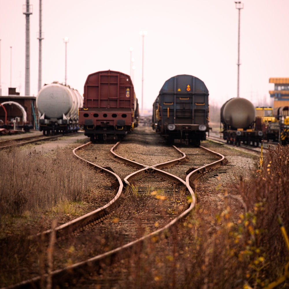 blue and black train on rail tracks during daytime