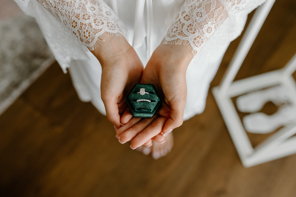 person holding black and green container