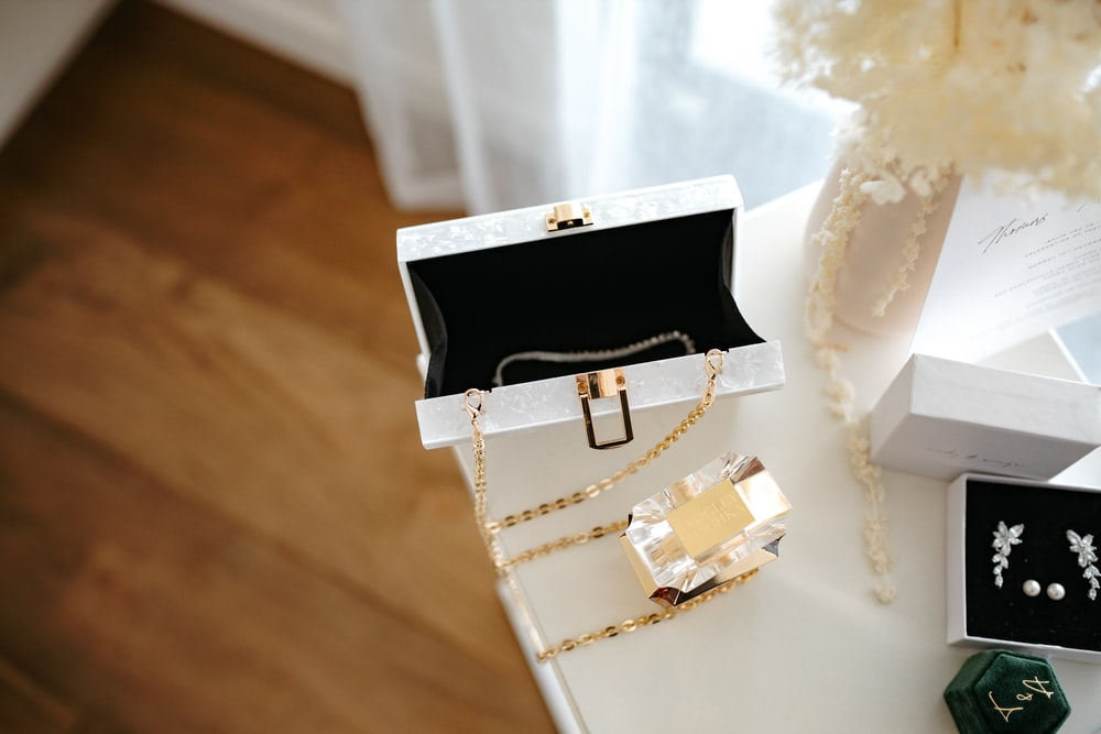 gold and silver gift box on white textile