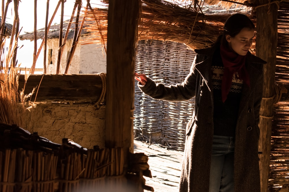 woman in black jacket standing on brown wooden plank