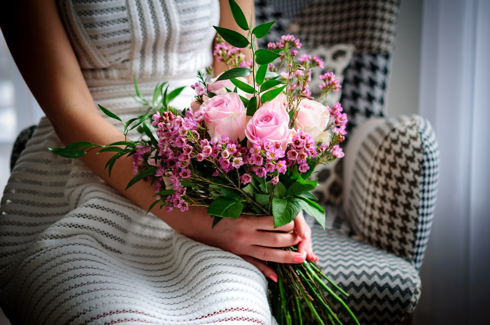 woman holding pink and white roses bouquet