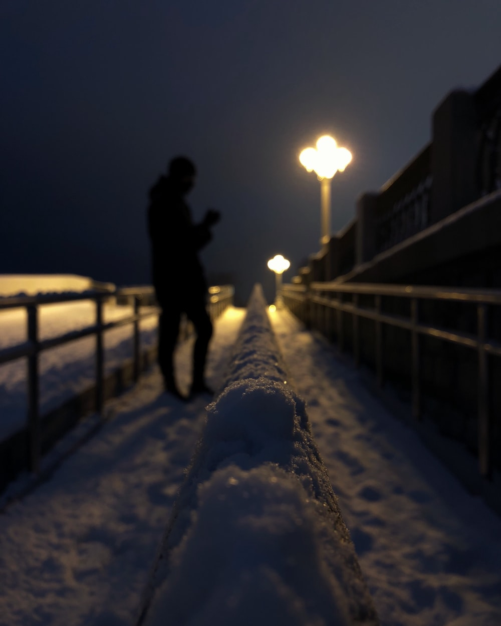 man in black jacket standing on snow covered ground during night time