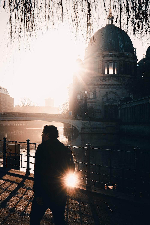 man in black jacket sitting on bench near body of water during daytime