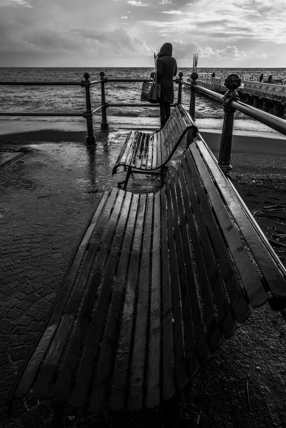 grayscale photo of person walking on wooden dock
