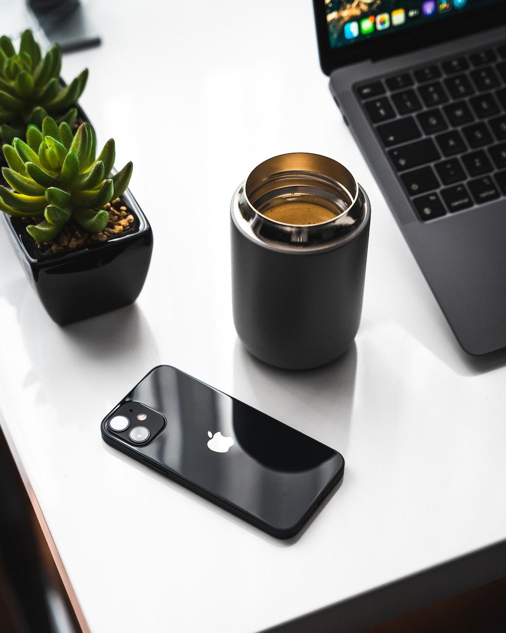 silver iphone 6 beside black ceramic mug on white table
