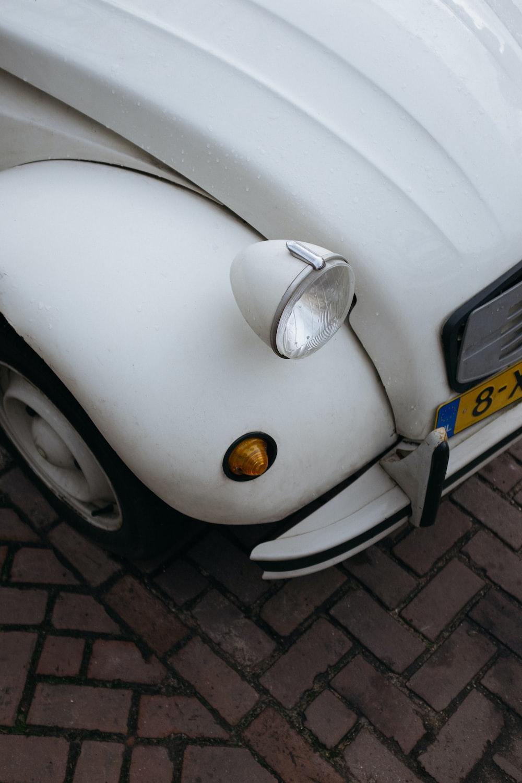white volkswagen beetle on gray brick floor