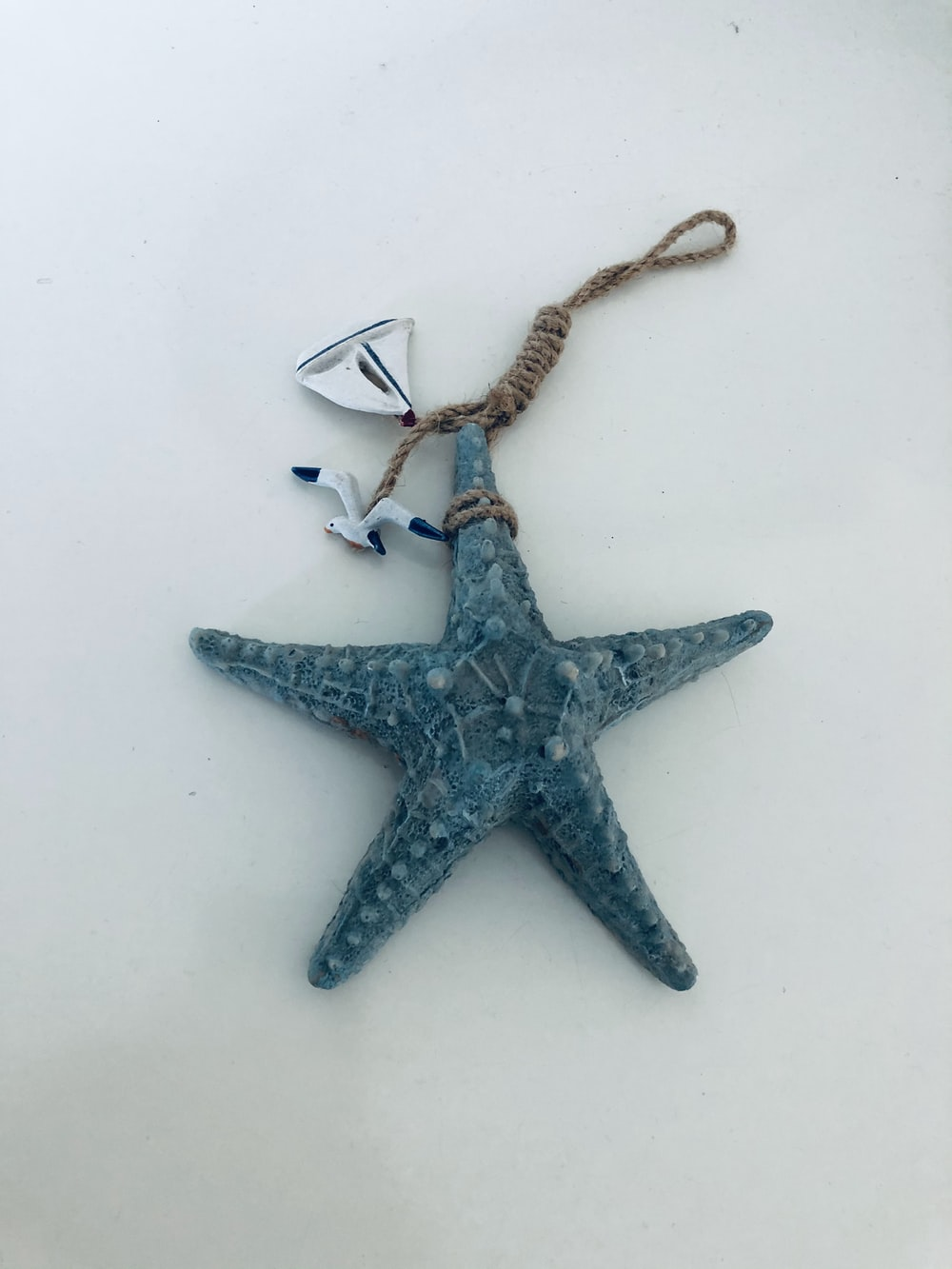 silver star pendant necklace on white surface