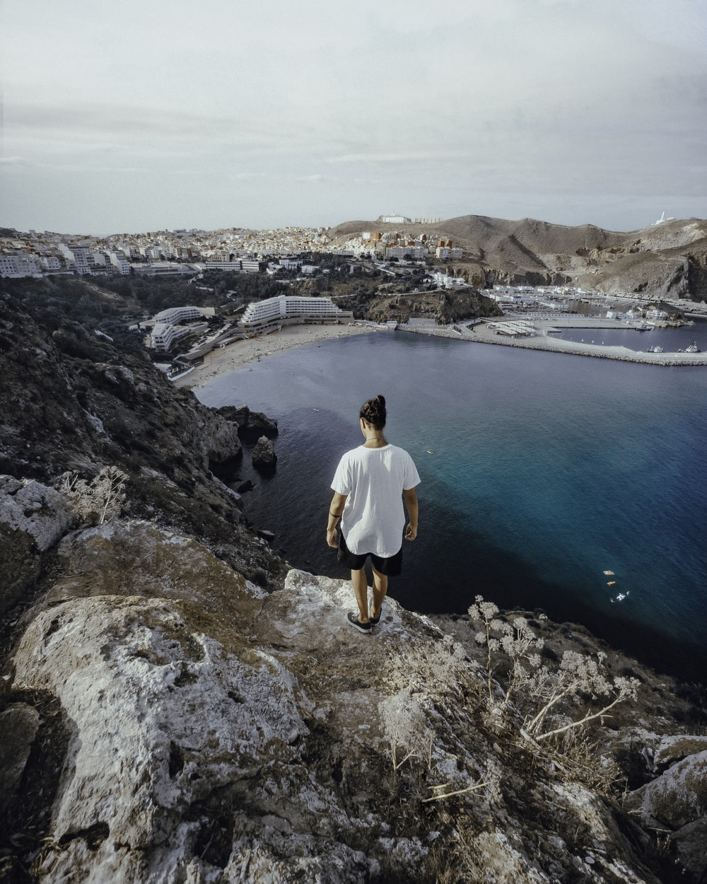 man in white long sleeve shirt and black shorts standing on rocky mountain looking at blue