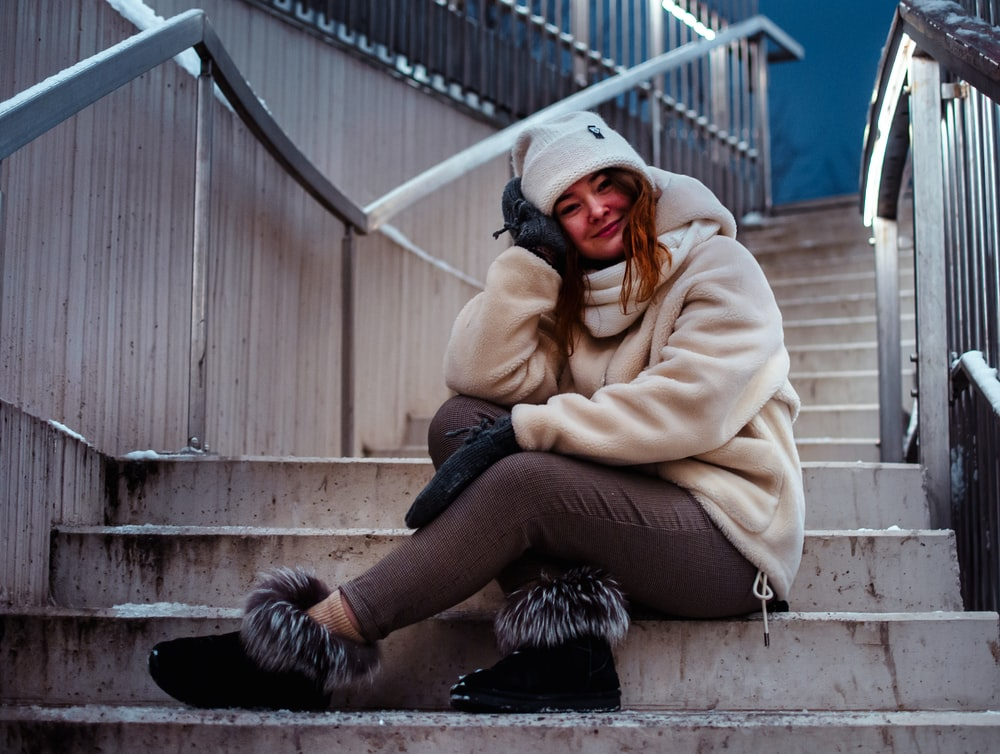 woman in beige coat and black pants sitting on stairs
