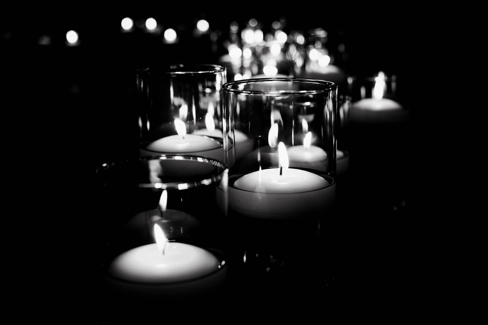 grayscale photo of candles on glass containers