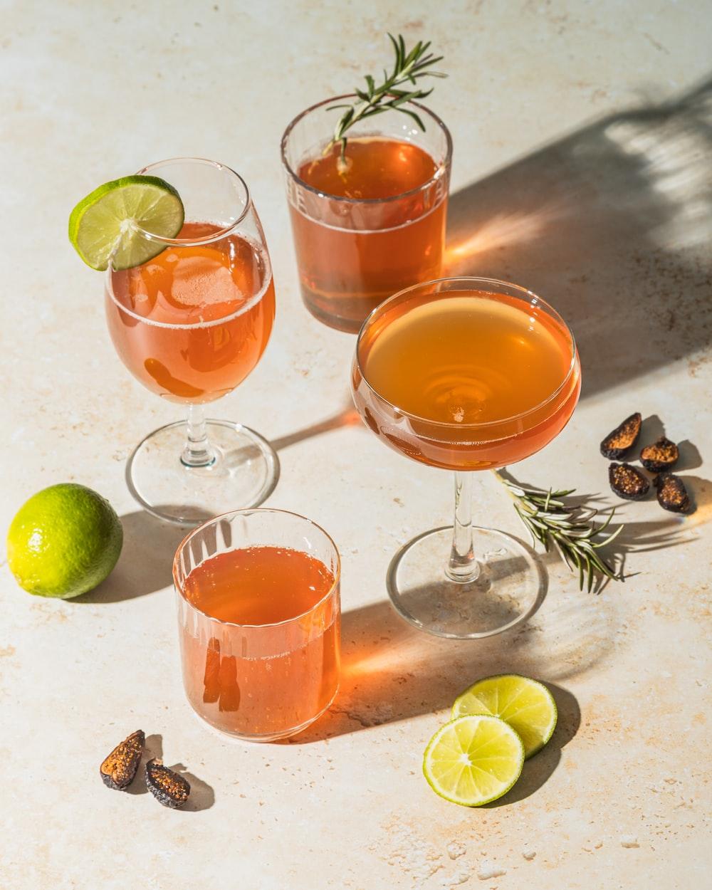 three clear drinking glasses with orange liquid
