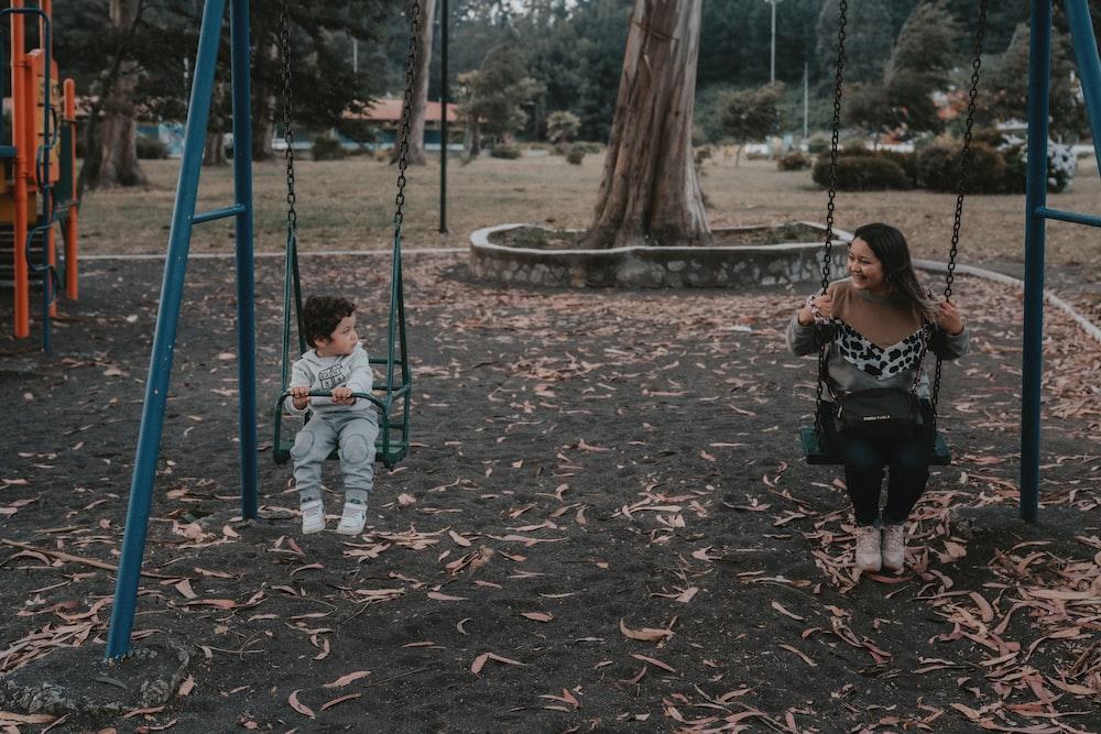 2 children sitting on swing during daytime