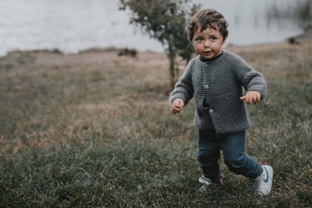 boy in gray sweater and blue denim jeans standing on green grass field during daytime
