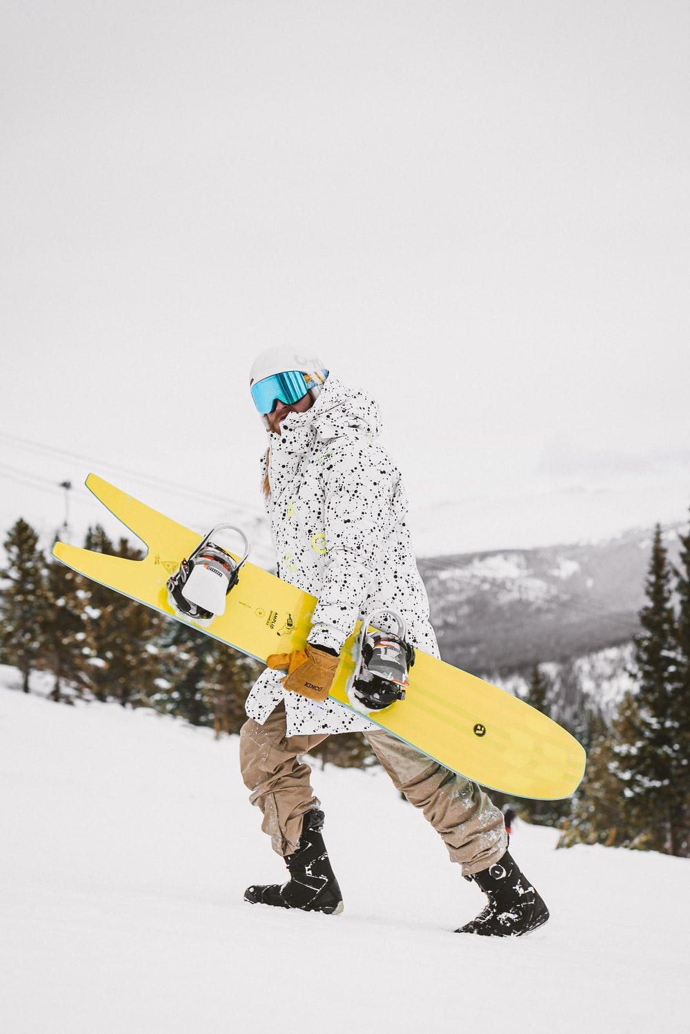 man in white and green jacket and brown pants holding yellow snowboard during daytime
