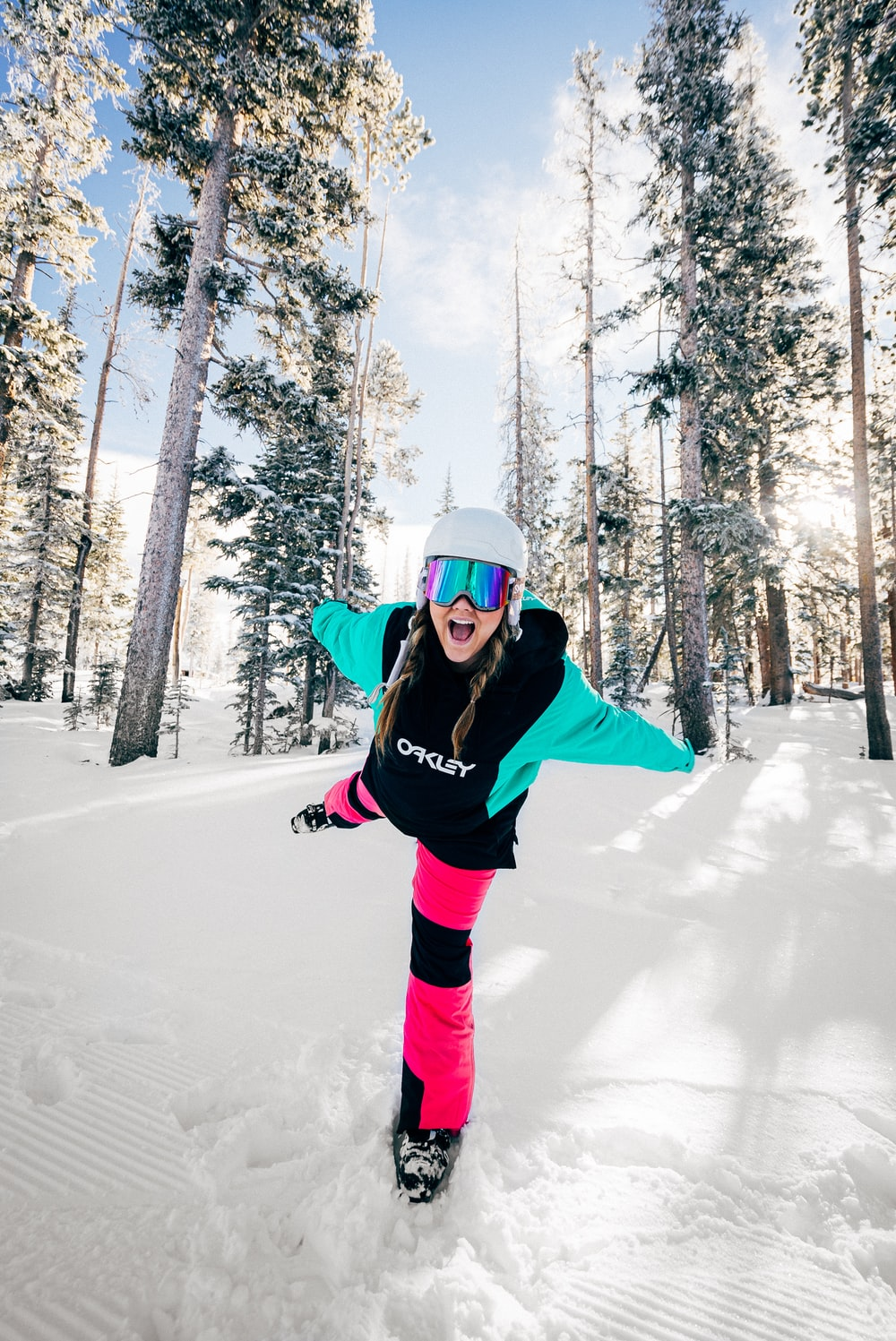woman in black jacket and pink pants standing on snow covered ground during daytime