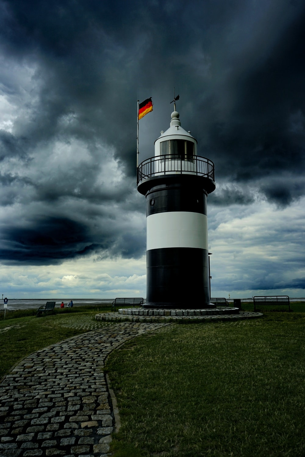 white and black lighthouse under cloudy sky during daytime