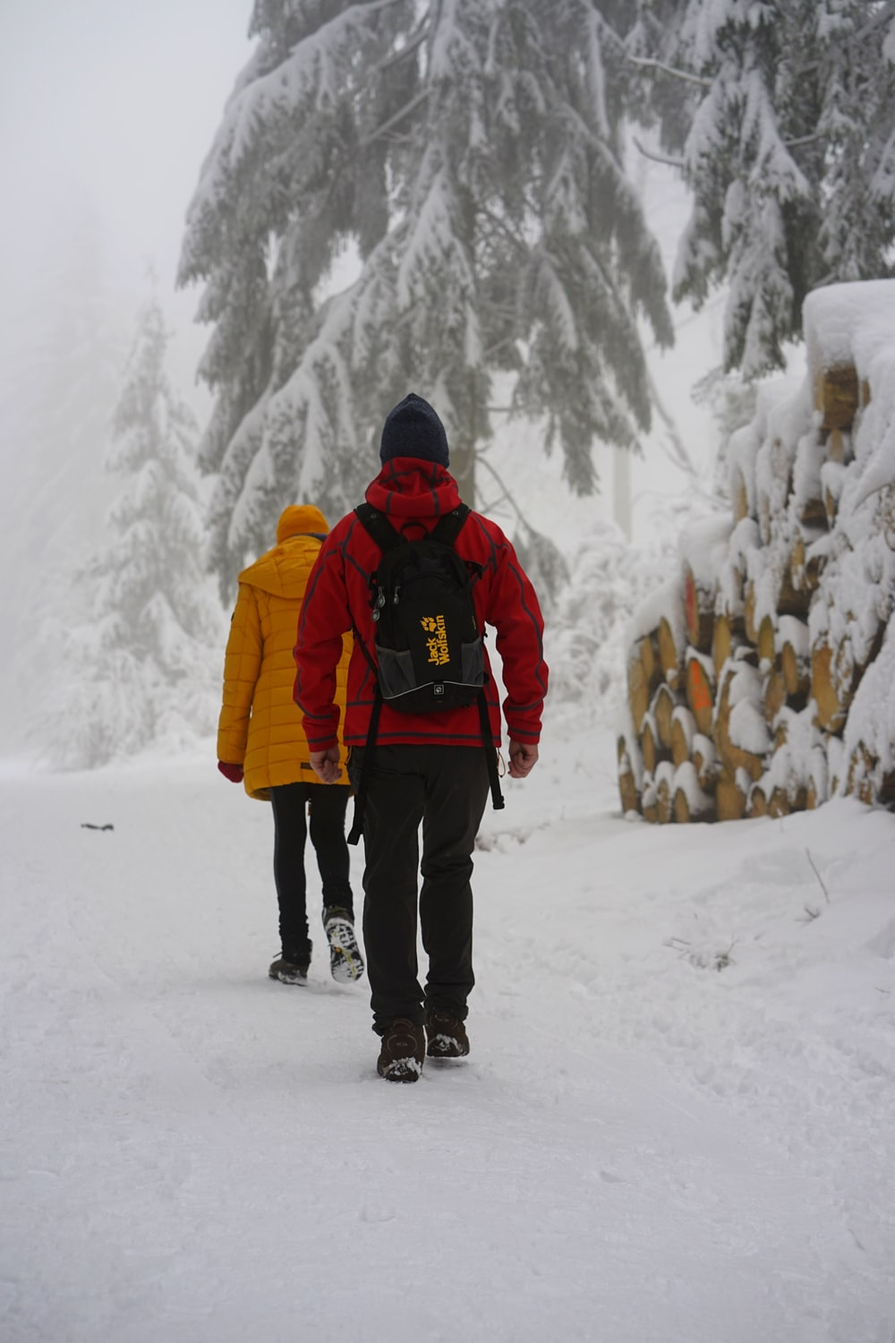 man in red and black jacket standing on snow covered ground during daytime