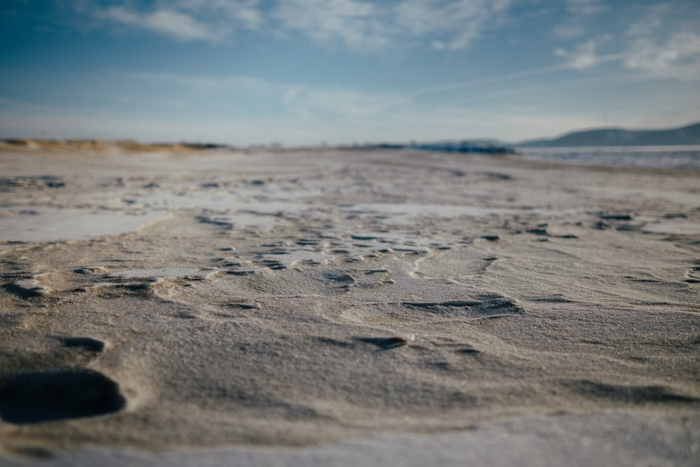gray sand under blue sky during daytime