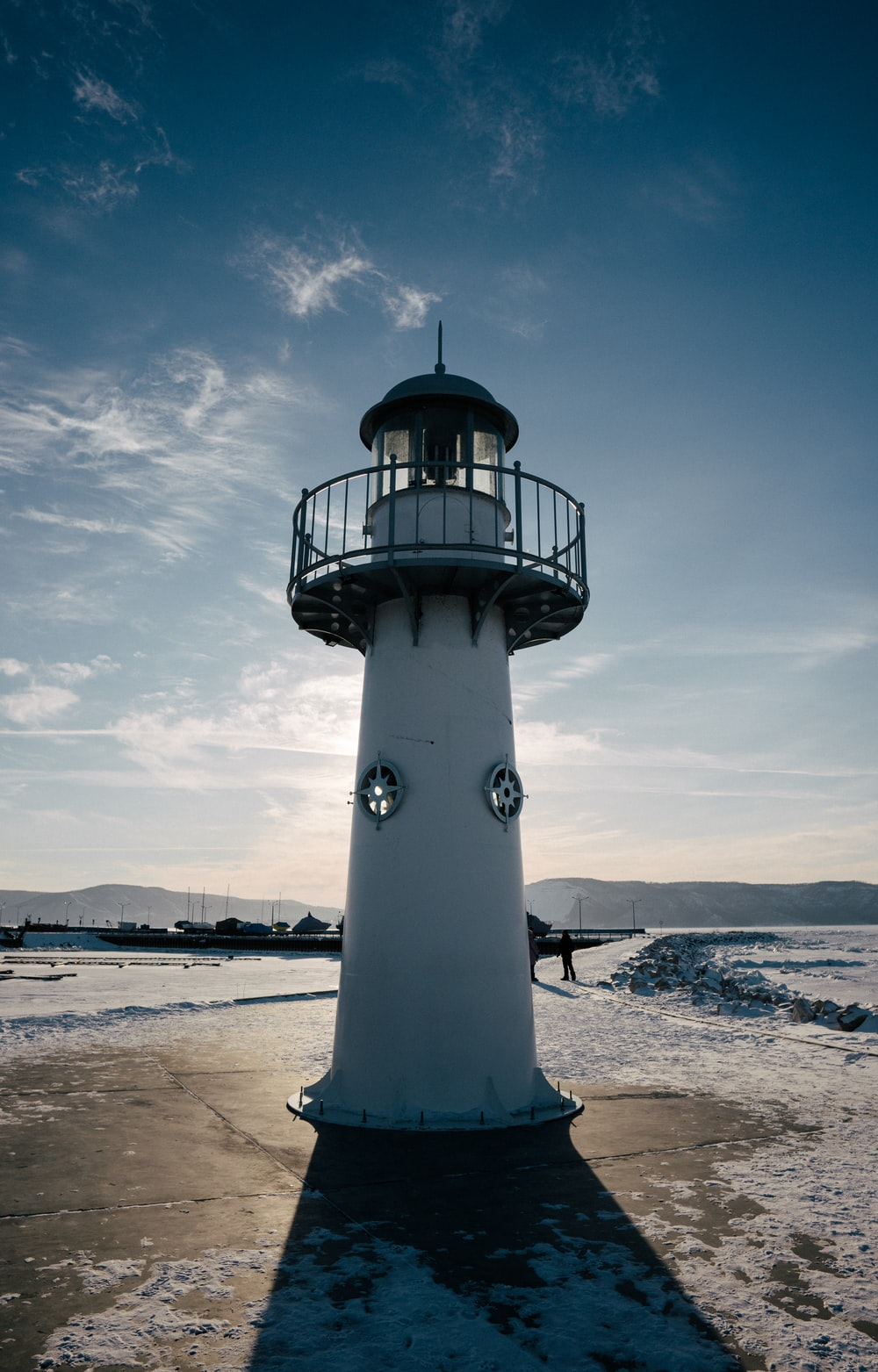 white and black lighthouse on beach under blue and white sunny cloudy sky during daytime