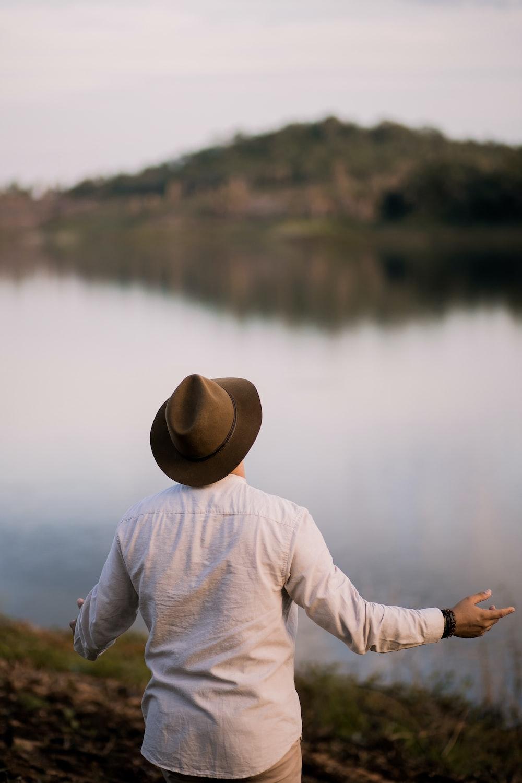 person in white long sleeve shirt wearing brown fedora hat standing near lake during daytime