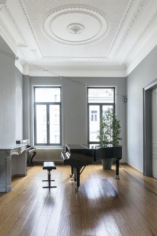 black grand piano near window
