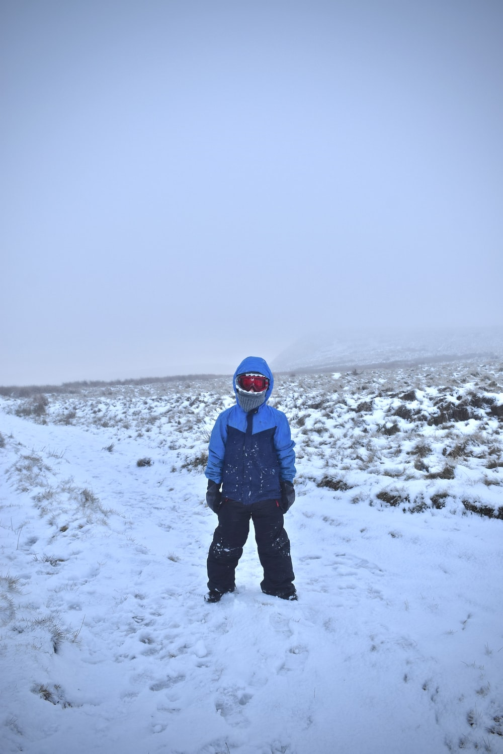 person in blue jacket and black pants standing on snow covered ground during daytime