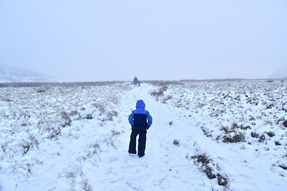 person in blue jacket walking on snow covered field during daytime