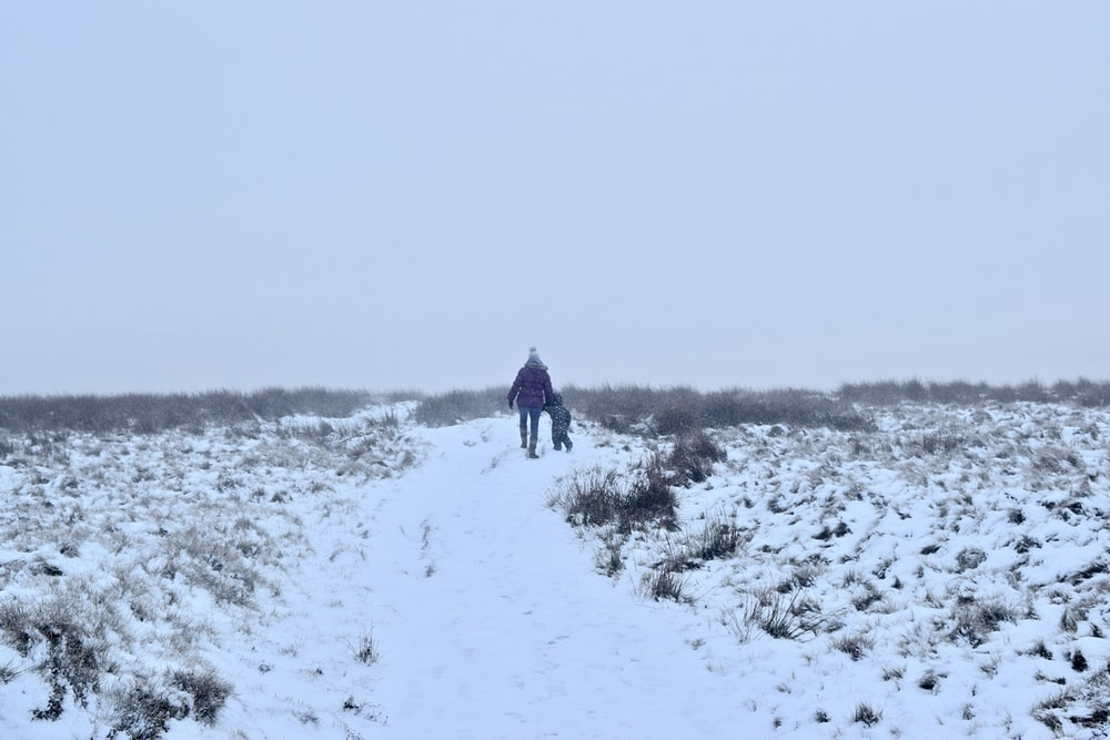 person in black jacket walking on snow covered field during daytime