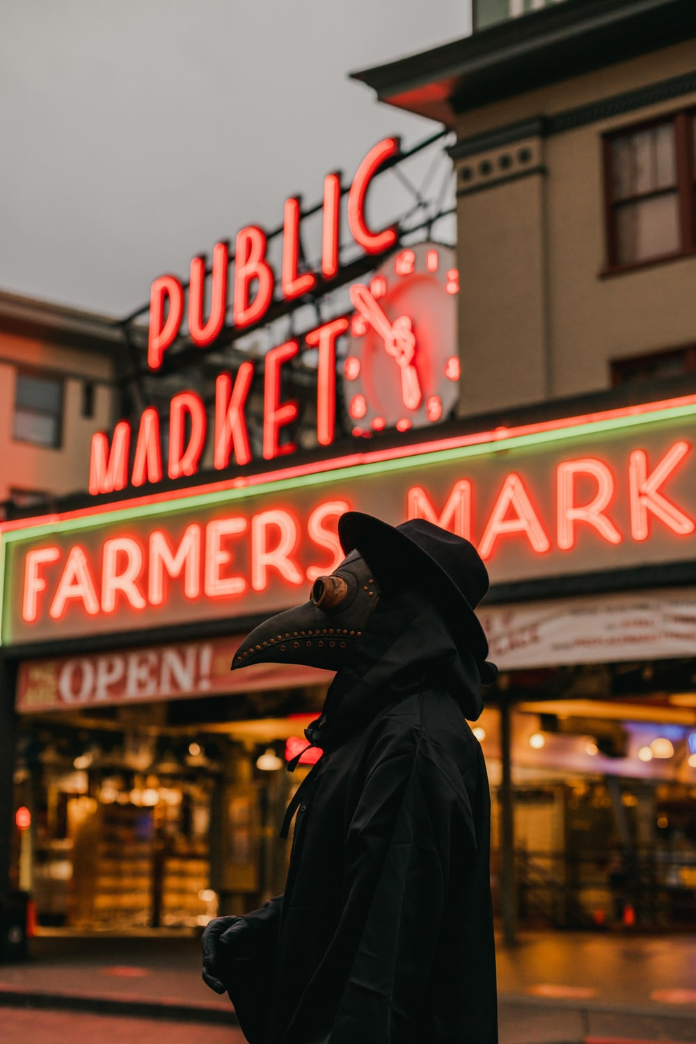 man in black leather jacket standing in front of store during night time