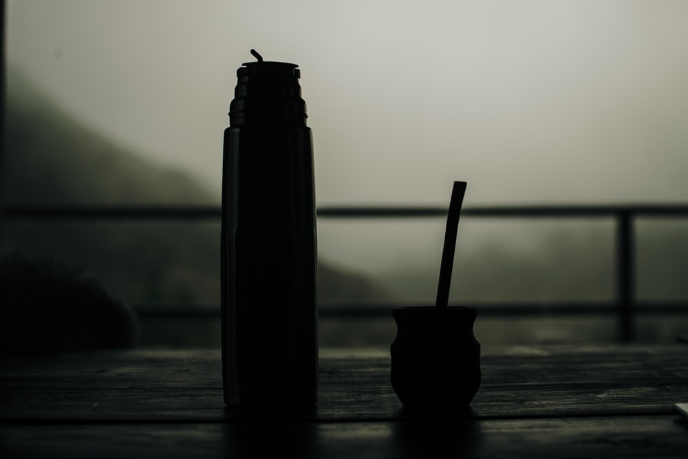 black bottle with white straw on brown wooden table