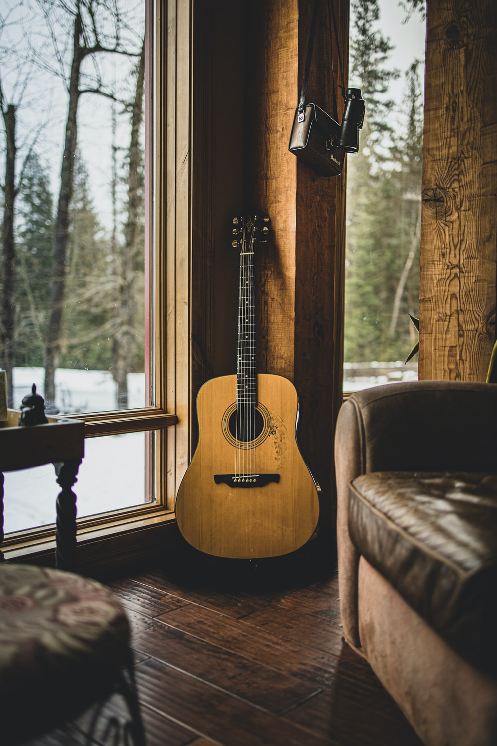 brown acoustic guitar on brown wooden chair